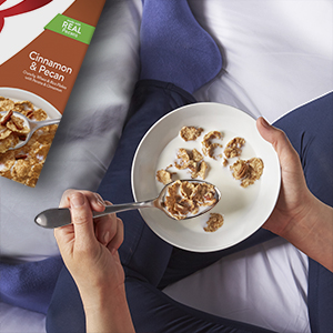 Enjoy cereal with milk at night as a treat like this young woman in leggings relaxing on her bed