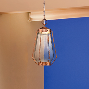 Washed copper outdoor pendant light hung from beige ceiling with evening skies in the background.
