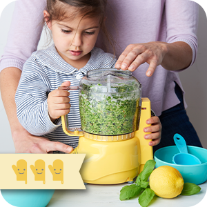 Image of young girl using a food processor, with adult supervision.