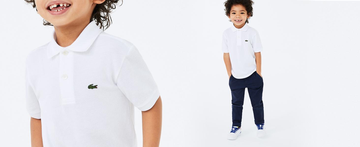 Niño pequeño con polo clásico blanco y pantalón negro