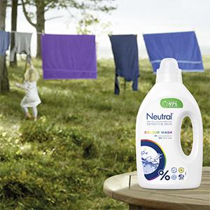 Neutral wasmiddel op voorgrond, waslijn met gekleurde was en blond meisje op de achtergrond