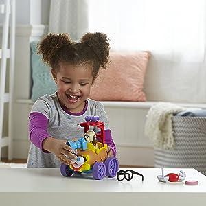 Criança encaixando diferentes peças no Mr. Potato Head em forma de veículo