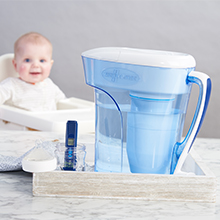 A baby smiling while looking at ZeroWater Water Filtration Pitcher