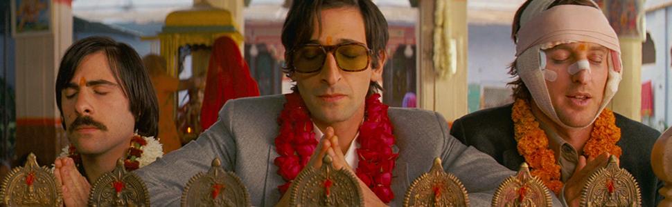 Jason Schwartzman, Adrien Brody, and Owen Wilson praying with colorful flower necklaces