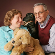 Founders Judy and Atis Folkmanis smiling and holding puppets.