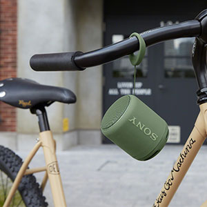 A SRS-XB10 speaker hanging from the handlebars of a bike