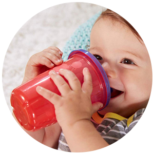 baby holding a red sippy cup