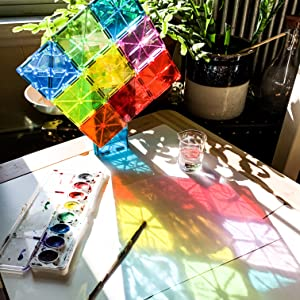 vibrant colors refracted through Magna-Tiles onto a white surface with washable paint beside
