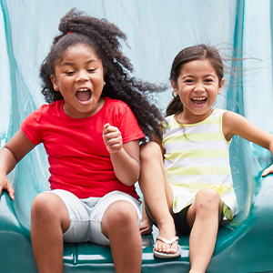 two girls going down a slide together