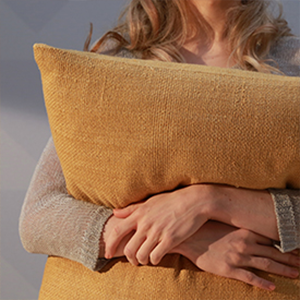 woman cuddling with yellow pillow