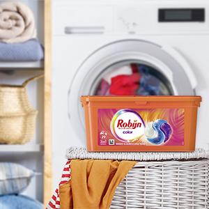 Een verpakking van de Robijn wascapules op een volle wasmand met bonte kleding voor een wasmachine