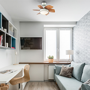 White 6 blade ceiling fan in small office or dorm room with sofa.