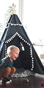 Young boy playing in front of his JumpOff Jo Teepee Tent
