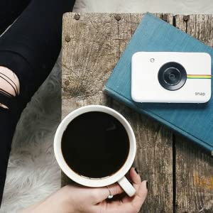 cup of coffee and a white instant camera