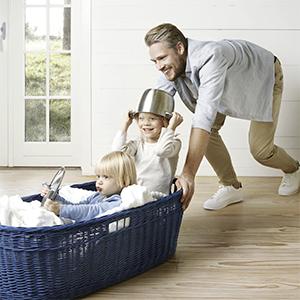 Twee kinderen spelen met keukengerei in gevlochten blauwe wasmand,  man duwt wasmand op houten vloer