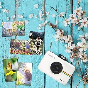 white camera next to photo prints