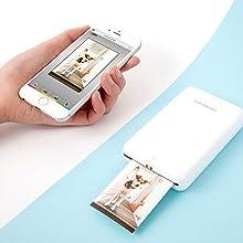 white zip mobile photo printer next to smartphone
