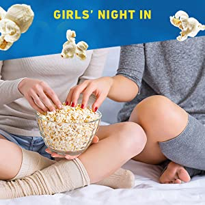 Teenagers enjoying microwave popcorn while watching movies on couch