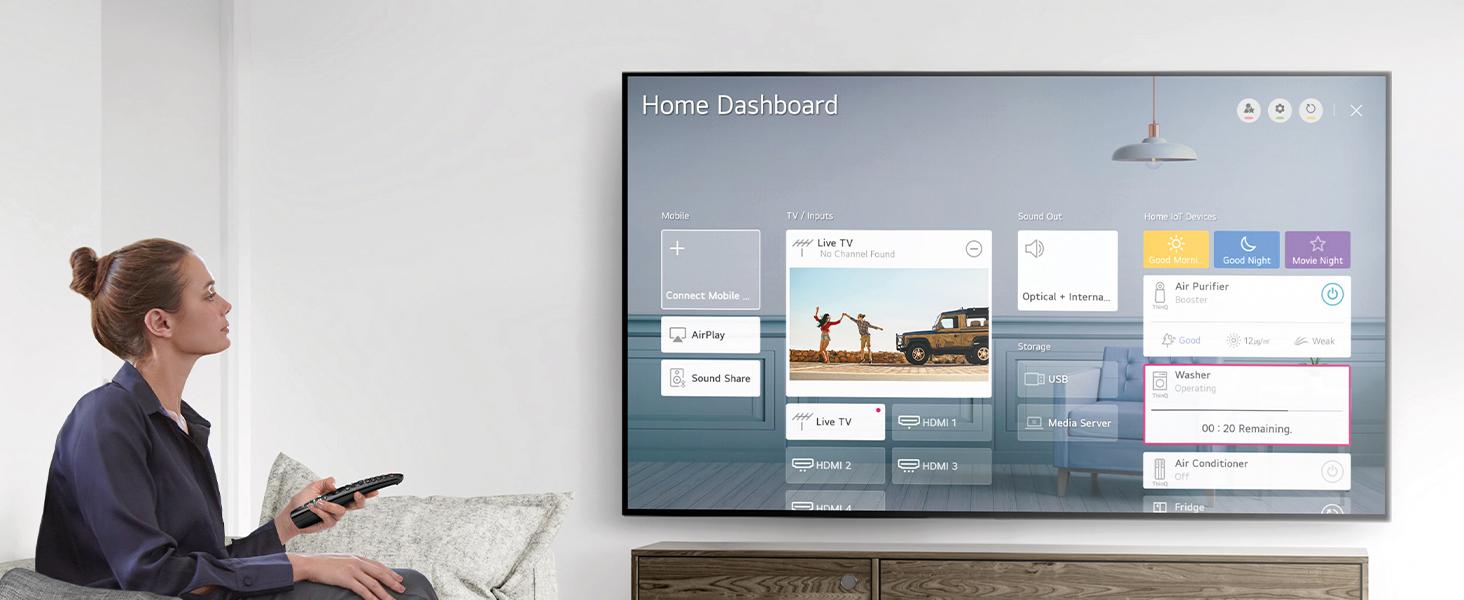 Eine frau sitzt im wohnzimmer, bedient ihr home dashboard auf dem nano-cell tv mit der magic remote