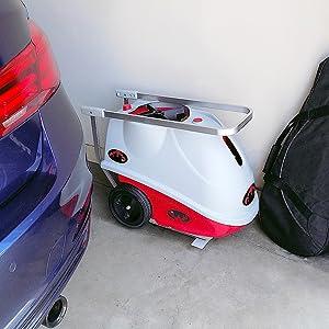 lobster elite tennis ball machine stored in garage next to BMW