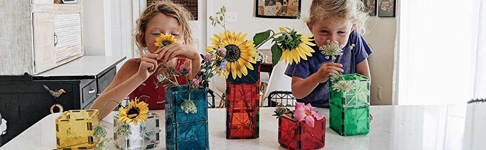 Two sisters stop and smell flowers they picked from Magna-Tiles vases