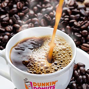 Coffee being poured into a Dunkin Donuts coffee mug resting on roasted coffee beans