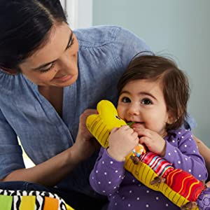 A baby holding Lamaze Musical Inchworm Toy