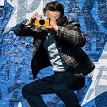 boy taking picture with yellow camera