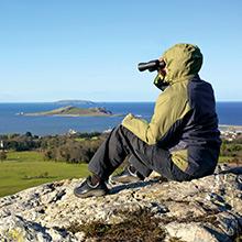 man sitting on montain rock looking through binoculars