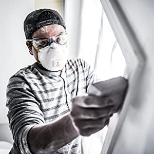 Man sanding windowsill with respirator on