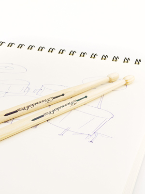 drumstick pencils resting on a notepad by a sketch of a drum kit