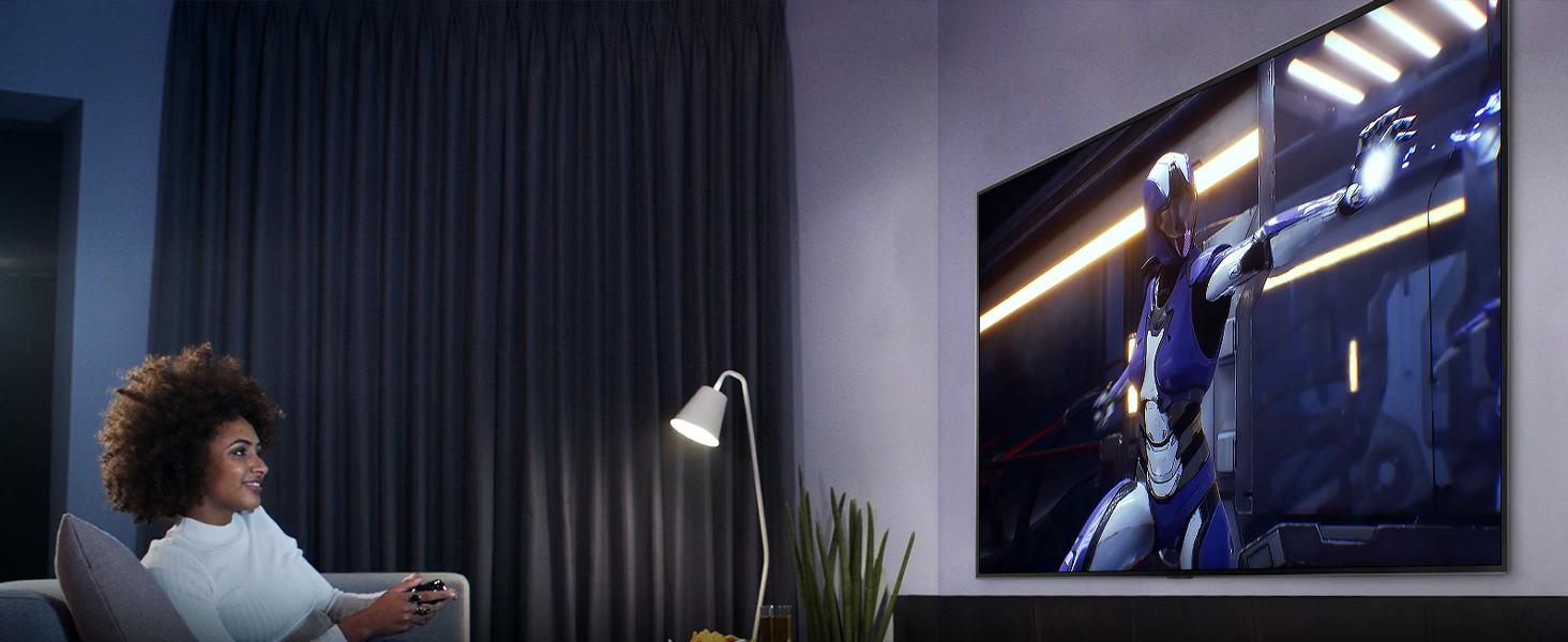 Jemand sitzt im wohnzimmer und genießt das hdr-gaming mit hgig des lg uhd tvs
