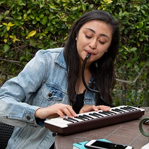 Girl seated playing pianica