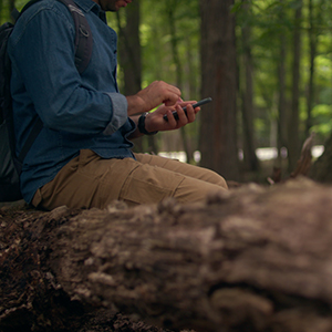 Person hiking in the woods using their smartphone