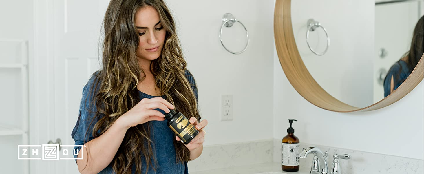 Healthy young woman with great hair opening her bottle of Hairfluence by Zhou Nutrition.