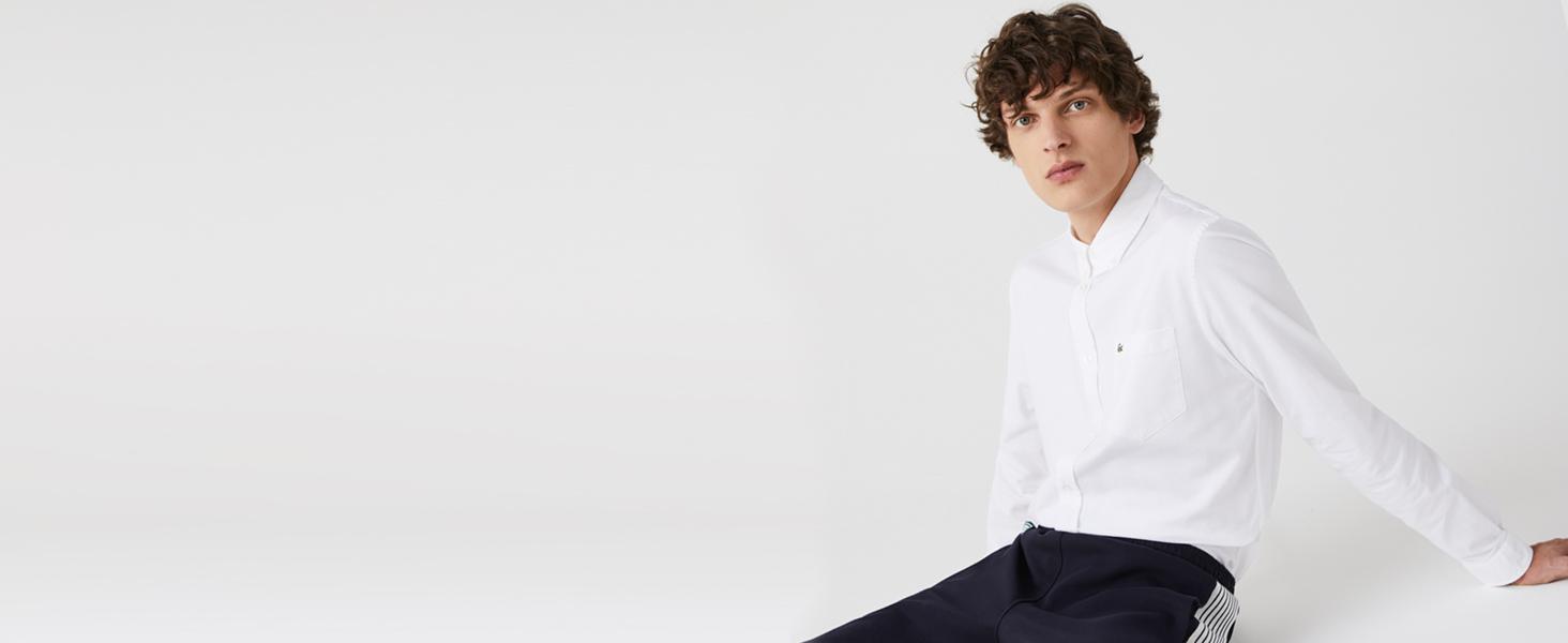 Hombre sentado con camisa blanca y pantalón de chándal
