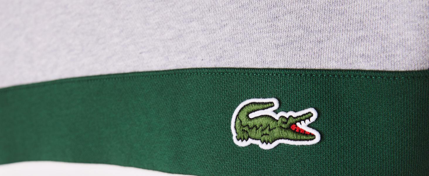 Detalle de cocodrilo bordado en el pecho de sudadera con líneas beis y verde Lacoste