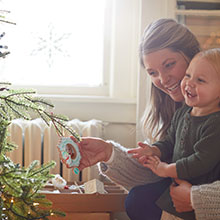 New mom with baby and a Hallmark Keepsake ornament celebrating their first Christmas