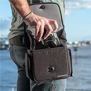 Hombre en el puerto sacando una cámara de la funda con una mano