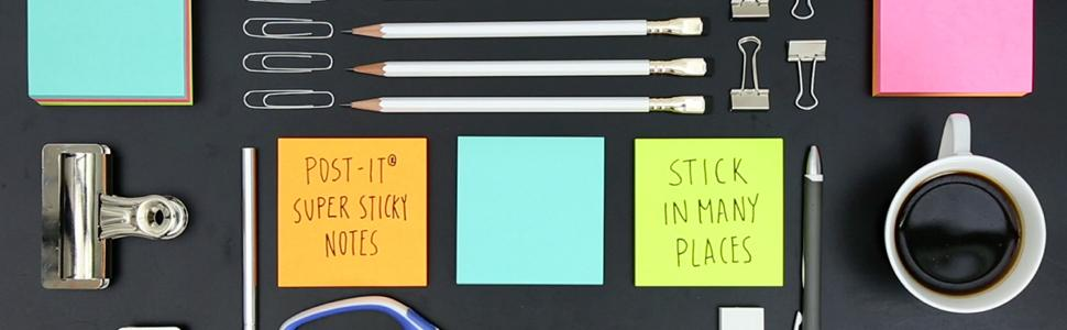 Top view of a black desk with Post-it Notes, pencils, paper clips, a pen and a cup of black coffee.