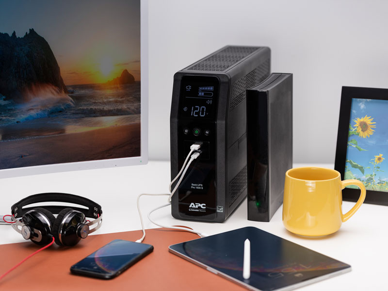 Smartphone and tablet plugged into the APC Back-UPS Pro in a home office