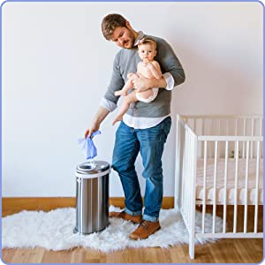 Diaper sacks are easy to use! Image of father disposing of diaper sack into Ubbi steel diaper pail.