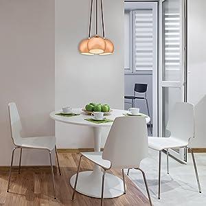 Trzy lekkie miedziane zawieszki wiszące na małym, nowoczesnym stole kuchennym.