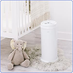 The Ubbi diaper pail is in a clean white nursery, to the right and nearby a crib and elephant plush