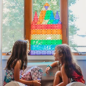 Two young girls playing with magnetic tiles against a brightly lit window showing vibrant colors