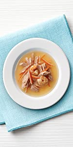 Bowl of broth with flakes of seafood and shrimp