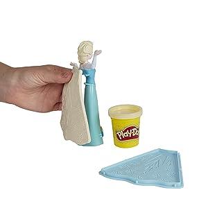 Criança colocando a capa feita de massinha na Elsa