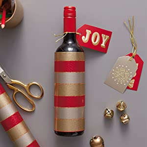 A wine bottle wrapped in red and gold stripped wrapping paper for hostess gifts and holiday dinners