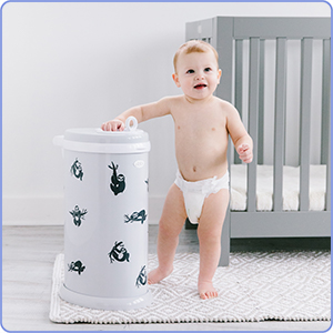 Baby standing and holding onto an Ubbi diaper pail with sloth nursery decals affixed on it