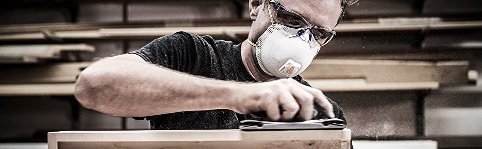Man sanding drawer while wearing respirator